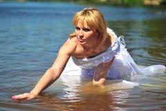 Das Mädchen in einem Hochzeitskleid im Wasser Stockfotos