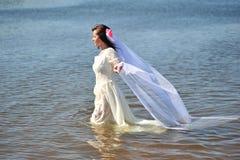 Das Mädchen in einem Hochzeitskleid im Wasser Stockfoto