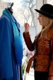 Das Mädchen in einem Hut kauft einen Mantel im System Lizenzfreies Stockfoto