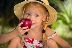 Das Mädchen in einem Hut mit rotem Apfel Stockfoto