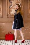Das Mädchen in einem Mantel mit einer roten Tasche Lizenzfreie Stockfotos