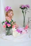 Das Mädchen in einem rosa Kleid mit einer Blume auf ihrem Kopf Lizenzfreies Stockbild