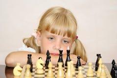Das Mädchen in einem rosafarbenen Kleid spielt ein Schach Lizenzfreie Stockfotografie