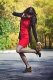 Das Mädchen in einem roten Kleid mit Blättern auf Fersen Stockfoto