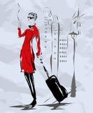 Das Mädchen in einem roten Mantel geht die Straße hinunter Lizenzfreies Stockfoto