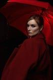 Das Mädchen in einem roten Mantel mit einem roten Regenschirm im Regen stockbilder