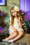 Das Mädchen in einem Sahnekleid mit lila Blumen Lizenzfreies Stockfoto