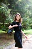 Das Mädchen in einem schwarzen Kleid mit einer schwarzen Tasche Lizenzfreie Stockbilder