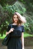Das Mädchen in einem schwarzen Kleid mit einer schwarzen Tasche Stockbild