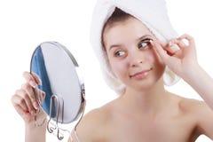 Das Mädchen in einem Tuch nachdem eine Dusche, Pastenwimpern, die in einem Spiegel schauen Lizenzfreies Stockfoto