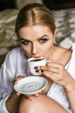 Das Mädchen in einem weißen Hausmantel mit einem Tasse Kaffee Frau hält eine weiße Kaffeetasse Stockfoto