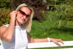 Das Mädchen in einem weißen Kleid sitzt auf einer Bank im Park in der Summe Lizenzfreie Stockfotos