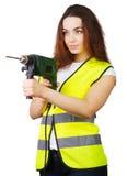 Das Mädchen in einer Bauweste mit einer elektrischen Bohrmaschine in den Händen Lizenzfreies Stockbild
