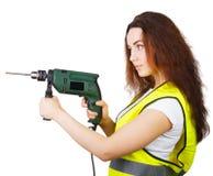Das Mädchen in einer Bauweste mit einer elektrischen Bohrmaschine in den Händen Lizenzfreie Stockfotos