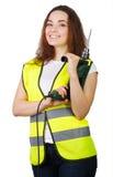Das Mädchen in einer Bauweste mit einer elektrischen Bohrmaschine in den Händen Stockfoto