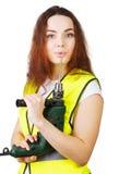 Das Mädchen in einer Bauweste mit einer elektrischen Bohrmaschine in den Händen Stockbild