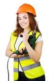 Das Mädchen in einer Bauweste und ein Sturzhelm mit einer elektrischen Bohrmaschine Lizenzfreie Stockfotos