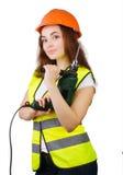 Das Mädchen in einer Bauweste und ein Sturzhelm mit einer elektrischen Bohrmaschine Stockfoto