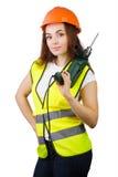 Das Mädchen in einer Bauweste und ein Sturzhelm mit einer elektrischen Bohrmaschine Lizenzfreie Stockbilder