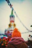 Das Mädchen in einer Kappe und in einem Schal vom hinteren, den Turm und die Weihnachtsdekorationen betrachtend Stockfoto