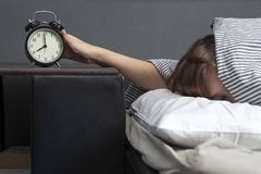 Das Mädchen, eingewickelt in einer gestreiften Decke, setzt heraus ihre Hand, um die Warnung abzustellen Es gibt acht Stunden auf Stockbild