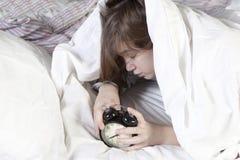 Das Mädchen, eingewickelt in einer weißen Decke, setzt heraus ihre Hand, um die Warnung abzustellen Es gibt acht Stunden auf dem  Lizenzfreie Stockbilder