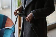 das Mädchen entfernt ihren grauen Mantel, unter dem ein blaues Kleid, den Gurt ihres Mantels lösend, im Raum ist zu Ihren äußeren lizenzfreie stockfotografie
