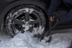 Das Mädchen entfernt Schnee vom Hinterrad ihres Autos, lizenzfreies stockfoto