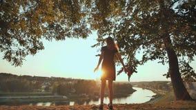 Das Mädchen enthusiastisch läuft, um den Sonnenuntergang auf dem Hintergrund der Stadt zu treffen und hebt ihre Hände an Video in stock video
