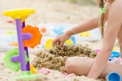 Das Mädchen errichtet eine Sandburgwand Stockfoto