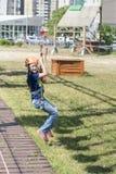 Das Mädchen fährt mit der Drahtseilbahn das Mädchen in der Drahtseilbahn reitet das Seil lizenzfreie stockbilder