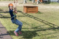 Das Mädchen fährt mit der Drahtseilbahn das Mädchen in der Drahtseilbahn reitet das Seil stockfotografie