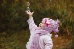 Das Mädchen fängt Seifenblasen im Herbst Lizenzfreies Stockbild