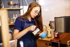 Das Mädchen fügt Milch der Schale mit Kaffee im Café hinzu Junge Frau barista, das in der Kaffeestube arbeitet stockfoto
