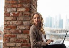 Das Mädchen am Fenster im Büro mit Laptop Lizenzfreies Stockbild