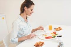 Das Mädchen frühstückt in der Küche Sie ` s, das Omelette und Saft isst Das Mädchen ist in einem hellen Raum Lizenzfreie Stockfotos