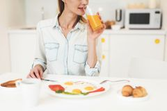 Das Mädchen frühstückt in der Küche Sie ` s, das Omelette und Saft isst Das Mädchen ist in einem hellen Raum Lizenzfreies Stockbild