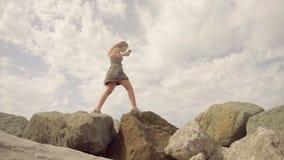 Das Mädchen geht auf den Berg und balanciert auf einem schmalen Kamm und hält einen Handy in ihrer Handzeitlupe stock video