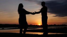 Das Mädchen geht, den Kerl zu treffen, schließen sich sie Händen gegen den schönen Sonnenuntergang und den Fluss an HD, 1920x1080 stock video