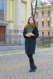Das Mädchen geht hinunter die Straße mit einem Buch Lizenzfreies Stockfoto