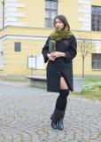 Das Mädchen geht hinunter die Straße mit einem Buch Lizenzfreie Stockbilder