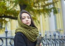 Das Mädchen geht hinunter die Straße mit einem Buch Lizenzfreie Stockfotos