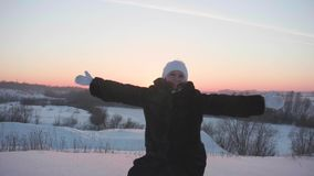 Das Mädchen geht in Winterholz, Würfe schneien, Lächeln, Lachen Wege in der Frischluft Sonnenuntergang stock footage