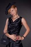 Das Mädchen, gekleidet worden im Schwarzen mit einem Beutel Stockfotos