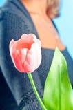 Das Mädchen gibt eine rosafarbene Blume Stockbild