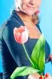 Das Mädchen gibt eine rosafarbene Blume Stockfotos