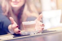 Das Mädchen gibt eine Schale Kaffeecappuccino lizenzfreie stockfotografie