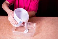 Das Mädchen gießt weiße Acrylfarbe in einem Plastikbehälter lizenzfreie stockfotos
