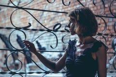 Das Mädchen am Gitter Windows lizenzfreies stockbild