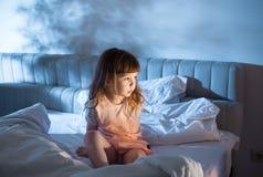 Das Mädchen glaubt der Entrüstung und sitzt auf dem Bett Lizenzfreies Stockfoto